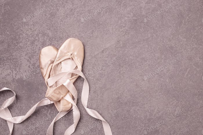 Ballet pointe shoes on pink background.