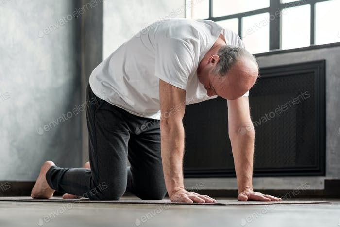 Senior bald yogi men practices yoga asana marjariasana or cat-cow pose