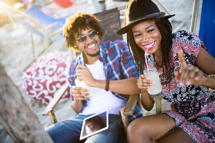 Junges glückliches schwarzes Paar mit Getränken entspannen am Strand