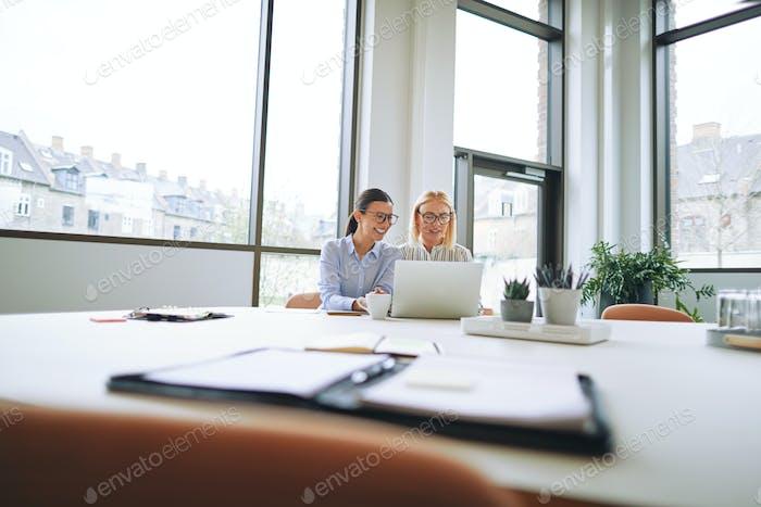 Две улыбающиеся бизнесмены сидят в офисе с помощью а ноутбук
