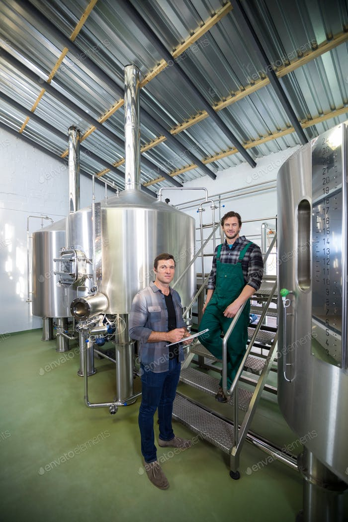 Coworkers standing by storage tank at brewery
