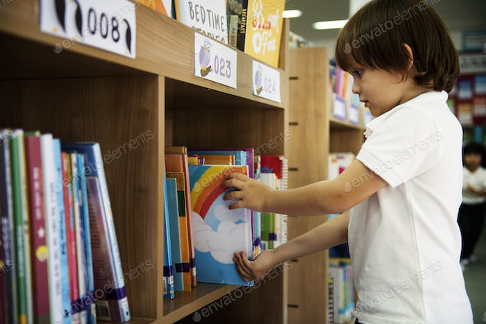 Young Boy Getting Children Story Book from Shelf in Library