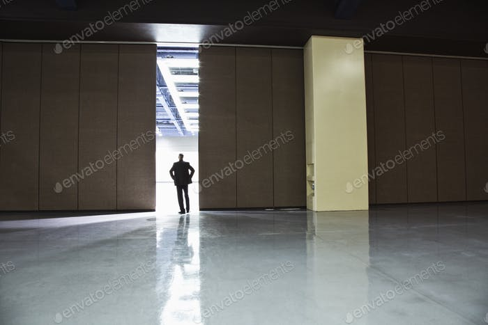 Businessman standing in a doorway between rooms in a convention center arena.