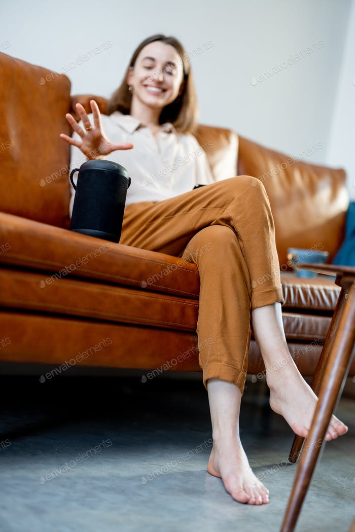 Woman speaking with audio assistant column on sofa