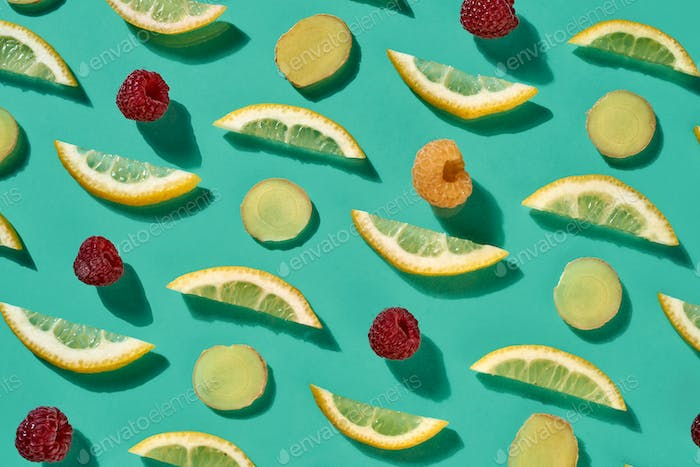 Fresh organic pattern from pieces of lemon and raspberry for healthy tea on a blue background. Food