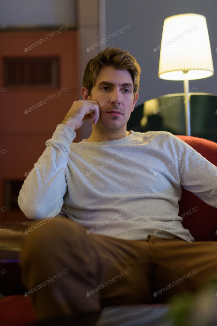 Portrait of handsome young Caucasian man sitting indoors