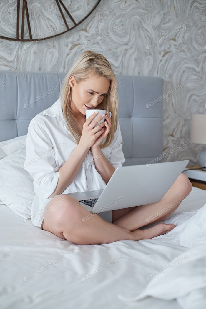 Happy beautiful woman working on a laptop sitting on the bed in the house