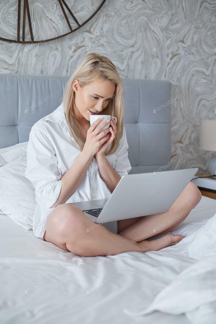 Glückliche schöne Frau arbeitet auf einem Laptop sitzen auf dem Bett im Haus