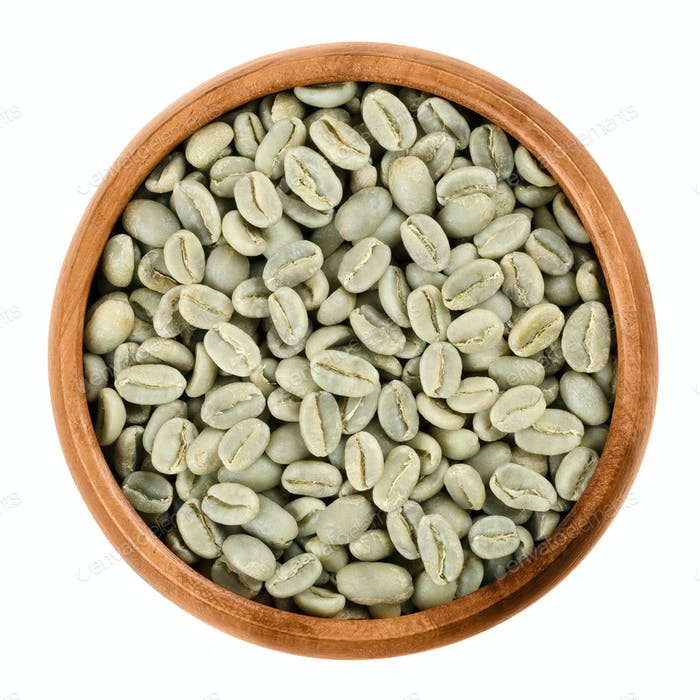 Green coffee beans in a wooden bowl over white