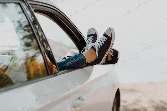 Woman's legs in sneakers in the window car with road map.