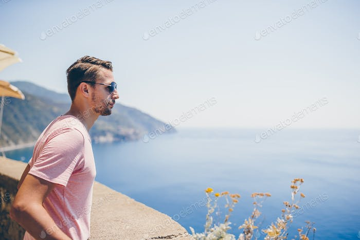 Rückansicht von jungen Mann Hintergrund atemberaubenden Dorf. Tourist Blick auf die malerische Aussicht von Manarola