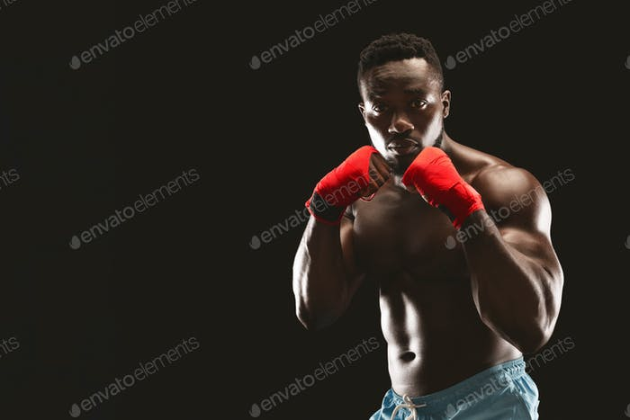 Athletic african fighter demonstrating classical boxing stance