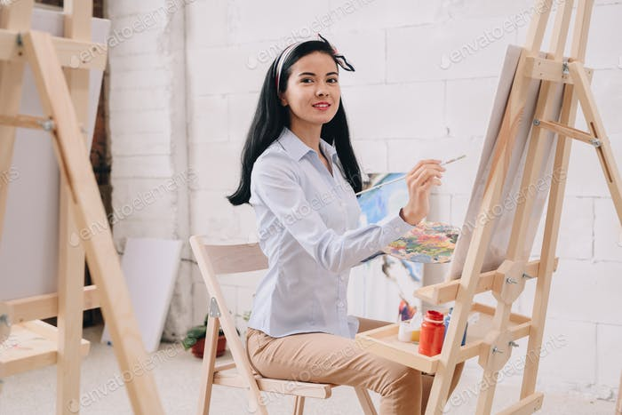 Young Woman Painting at Easel