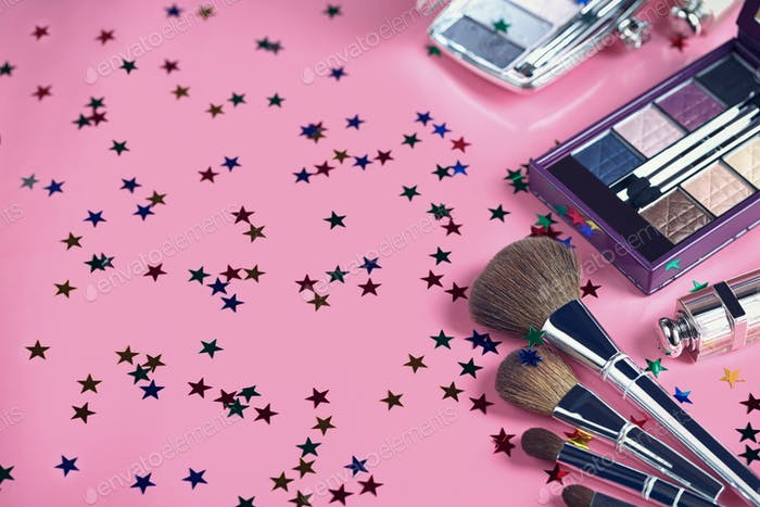 Makeup brush and cosmetics on a pink background