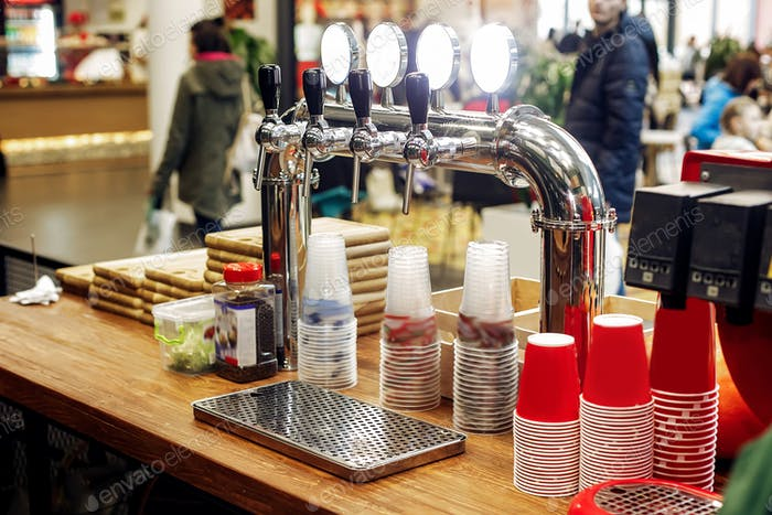 Beer bar with stylish taps and plastic cups  on wooden desk