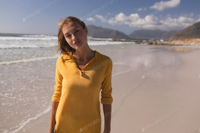 Portrait of young pretty woman standing on the beach on a sunny day