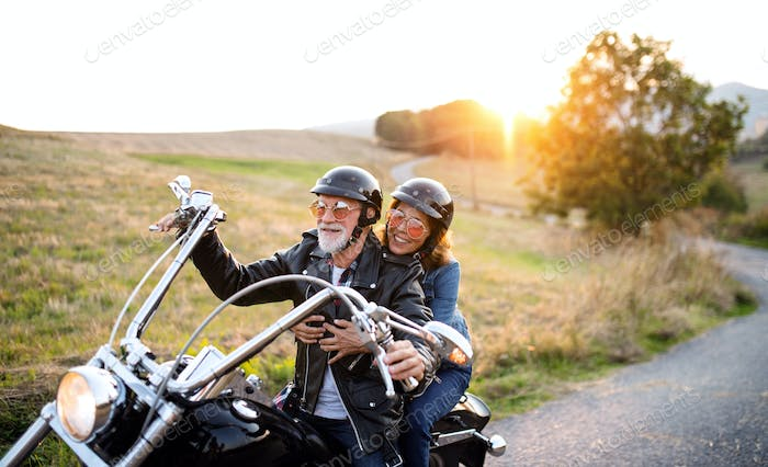 Cheerful senior couple travellers with motorbike in countryside at sunset.