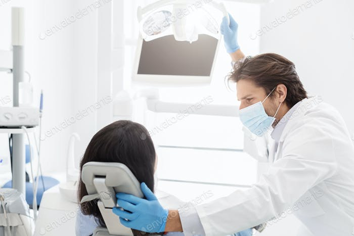 Attractive dentist comforting female patient sitting in chair