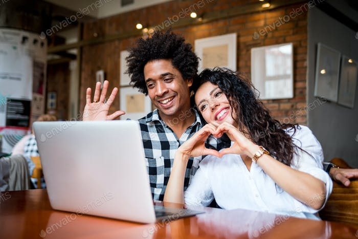 Multiethnic latin couple sitting together at cafe and video chatting using laptop