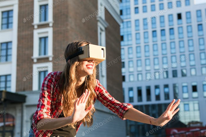 beautiful young girl with virtual reality VR headset on the street
