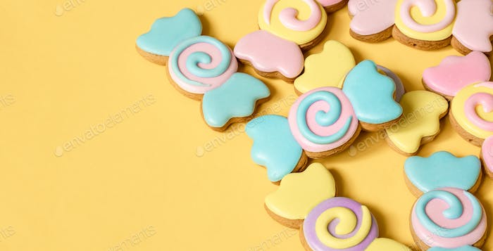 Bright cookies in glaze on a yellow background copy space.