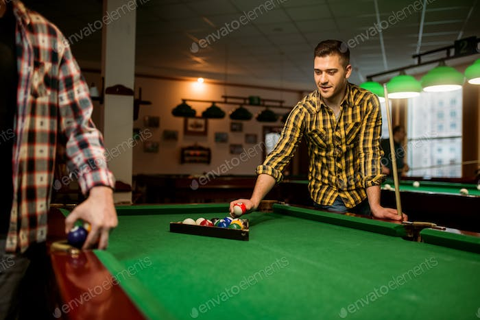 Two male billiard players places colorful balls