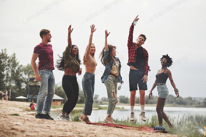 Foto de altura completa. Un grupo de personas tiene un picnic en la playa. Los amigos se divierten en el fin de semana