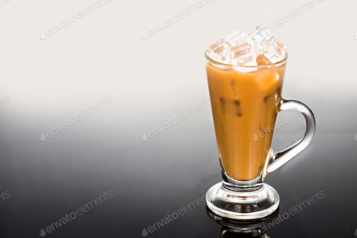 Refreshing ice cold coffee with milk in tall transparent glass