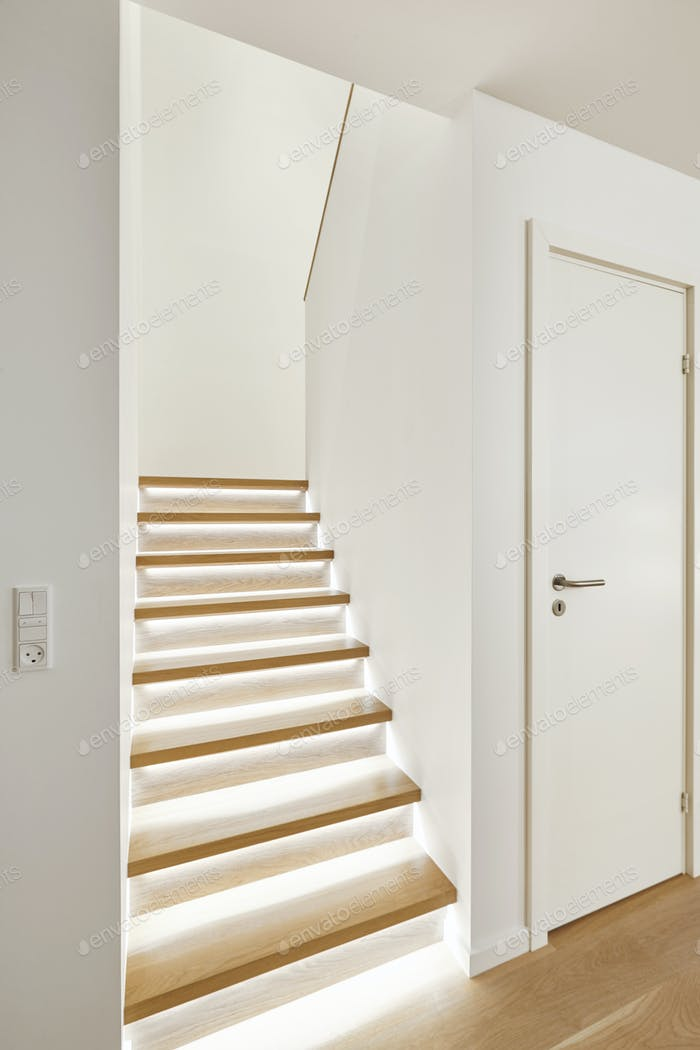 Home interior with stylish wooden iluminated staircase white walls. Vertical