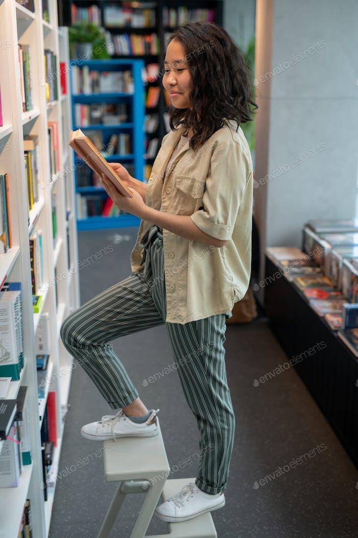 Cute Asian female student reading book by bookshelf