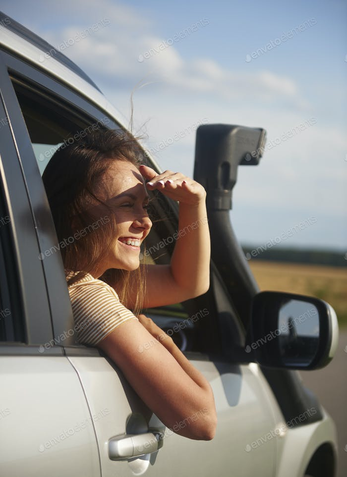 Happy young woman traveling by car and looking at view
