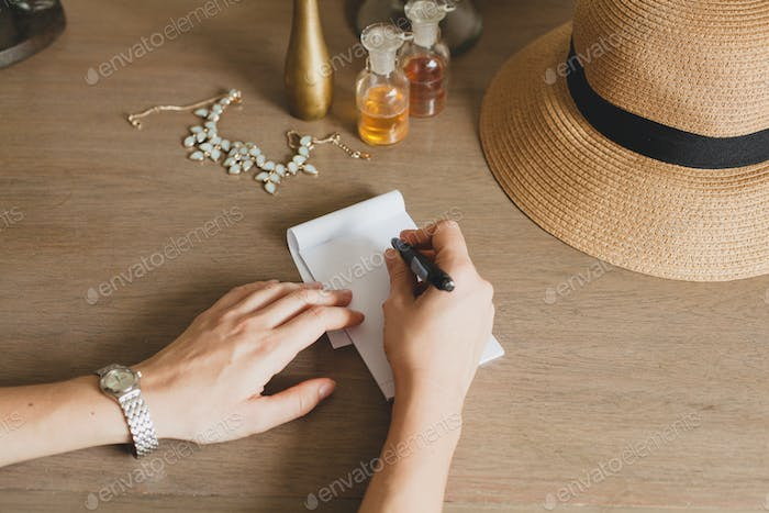 young stylish beautiful woman sitting at table in resort hotel room, writing a letter, holding pen