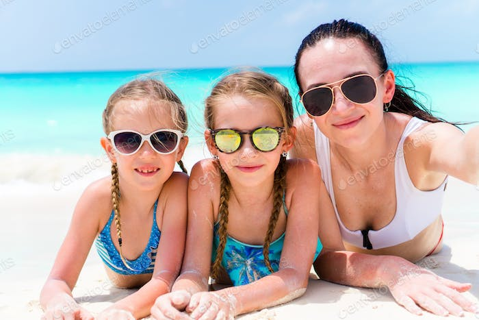 Mother and little girls taking selfie at beach lying on white sand. Happy family take selportrait