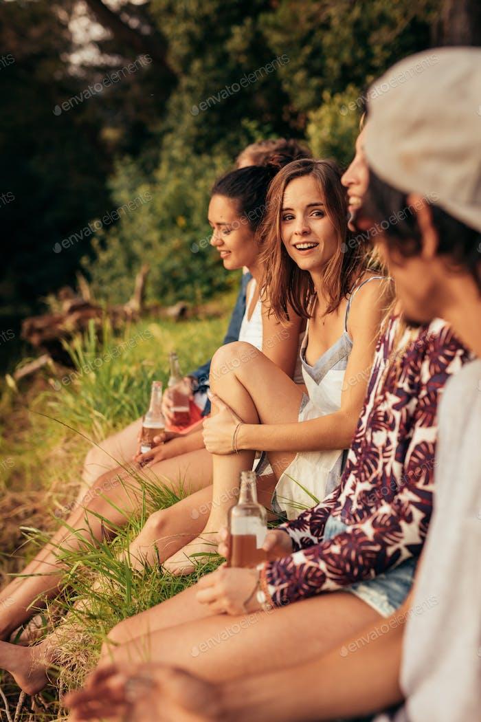 Junge Frau sitzt mit ihren Freunden an einem See