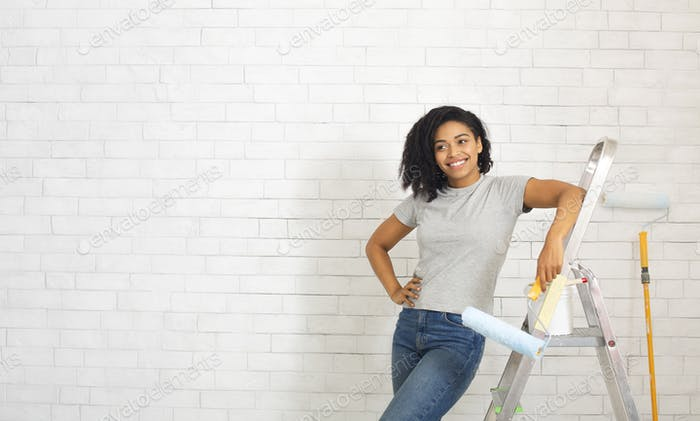 African american woman on stepladder with paint roller