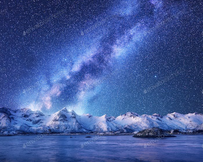 Purple Milky Way over snow covered mountains and sea at night