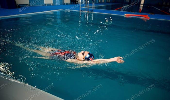 Женщина пловец плавание на ее спине в бассейн