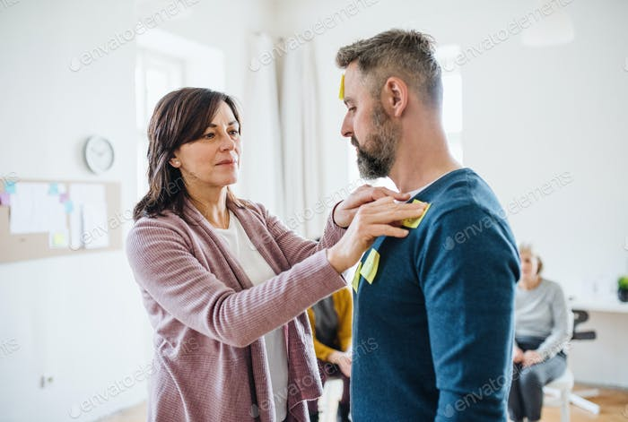 Counsellor putting an adhesive notes on client during group therapy.