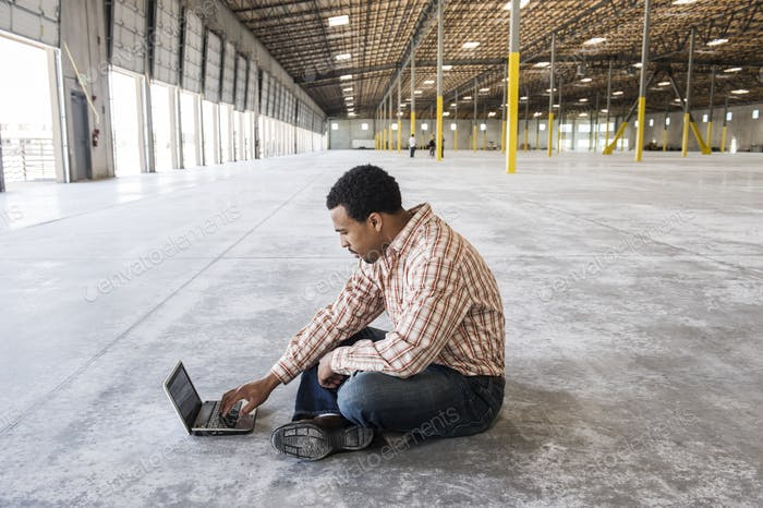 Black man working on lap top computer in front of loading dock doors in a new waerhouse.