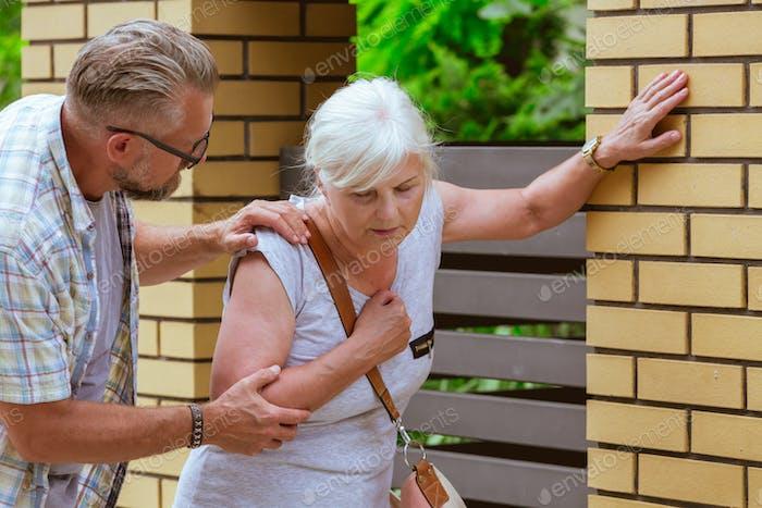 Mann unterstützt eine Seniorin fühlt sich unwohl auf der Straße