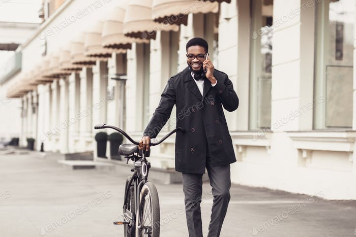 African-american businessman with bike walking and talking on cellphone