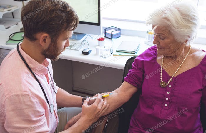 Male doctor giving an injection to senior female patient in clinic