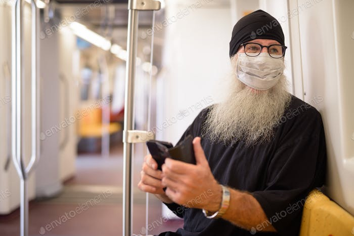 Mature bearded hipster man with mask thinking while using phone inside the train