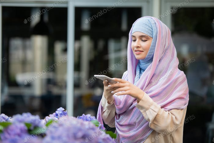 Young mobile female in hijab taking photo of flowers on smartphone camera