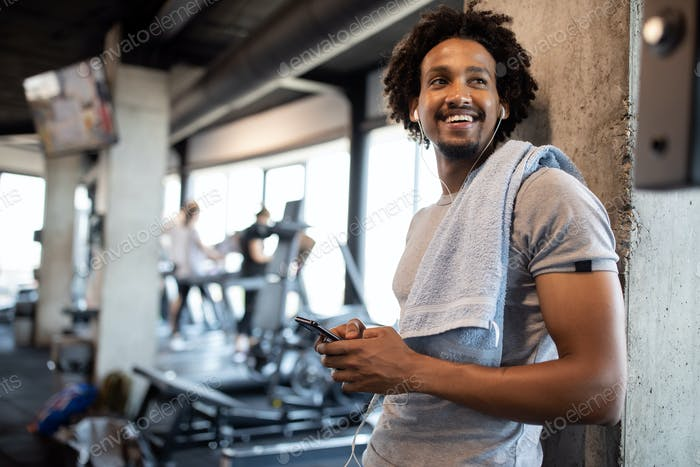 Young handsome man using phone while having exercise break in gym