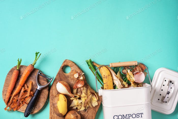 Garbage sorting. Organic food waste from vegetable ready for recycling in compost bin on blue