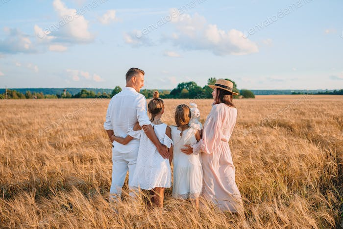 Happy family playing in a wheat field