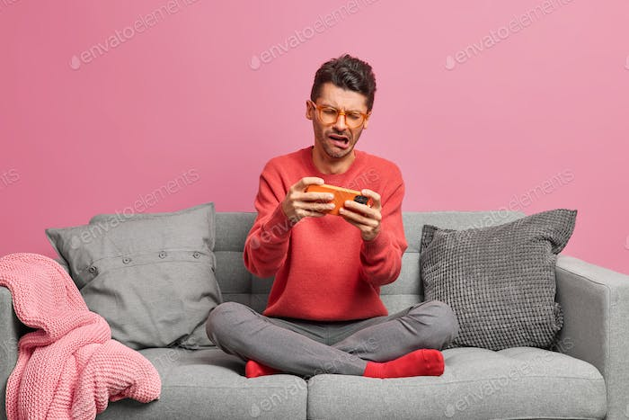 Upset male gamer sad to loose online championship uses mobile phone for playing video games poses cr