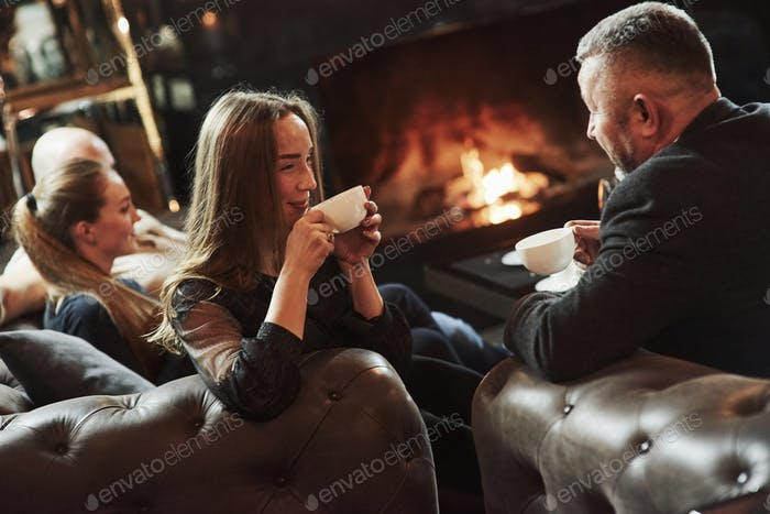 Family friends have nice evening near the fireplace in luxury modern restaurant