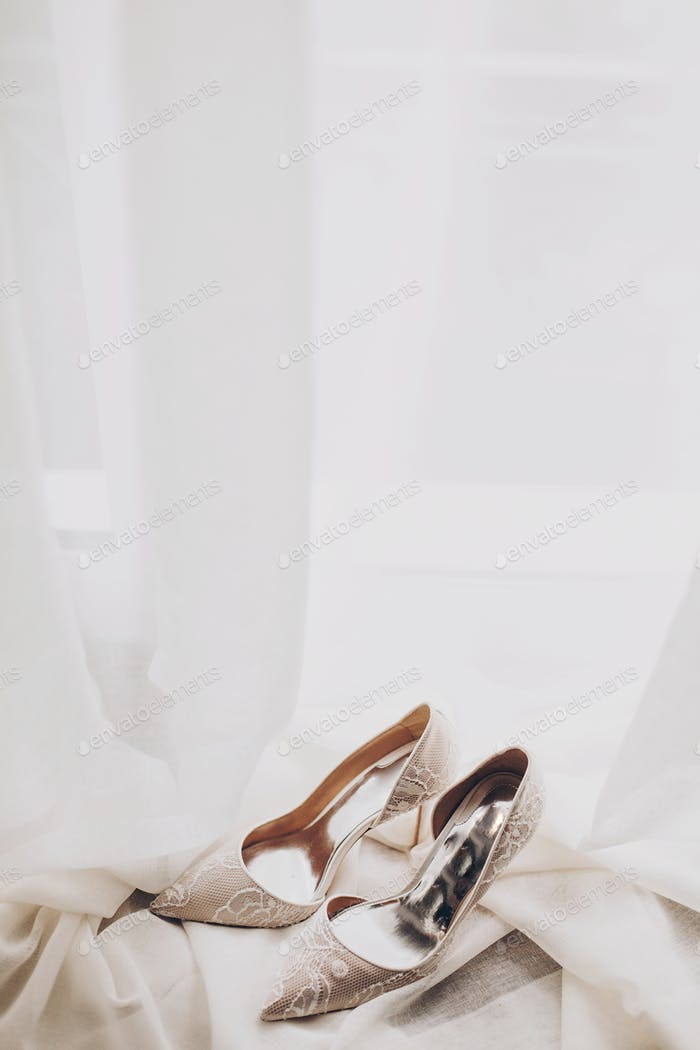 Modern wedding shoes on tulle in soft morning light